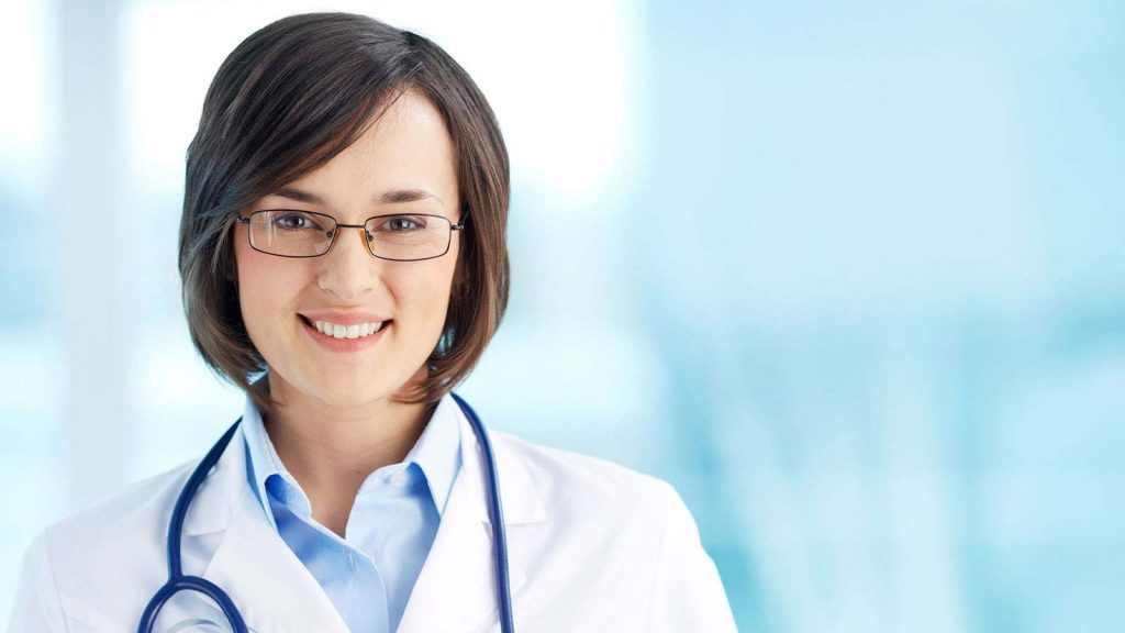 Female Doctor in uniform smiling with stethoscope resting around her neck