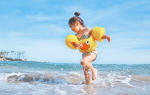 A little girl in summer beach, healthy after her paediatric consultation, Epping paediatrics clinic