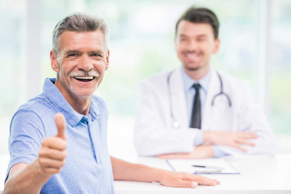Bulk billing doctor causes patient to smile and gesture thumbs up