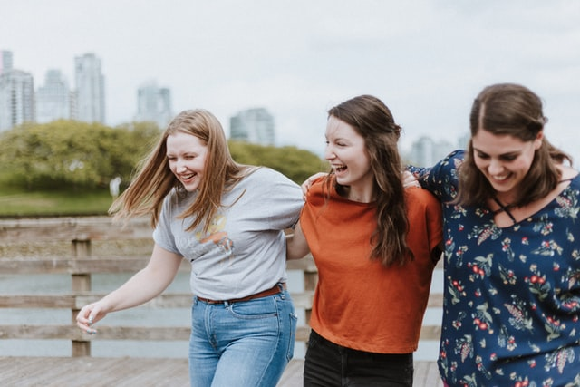A group of three female friends laughing together to reduce stress