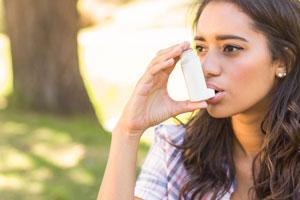 Female asthma sufferer using a Ventolin Inhaler