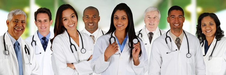 Team of doctors stand together ready to greet new GP colleague