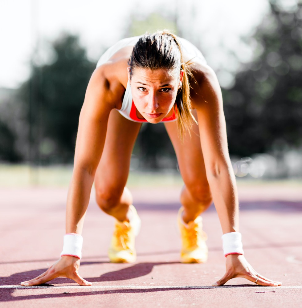 A woman athlete in track for a sprint, for keeping herself active