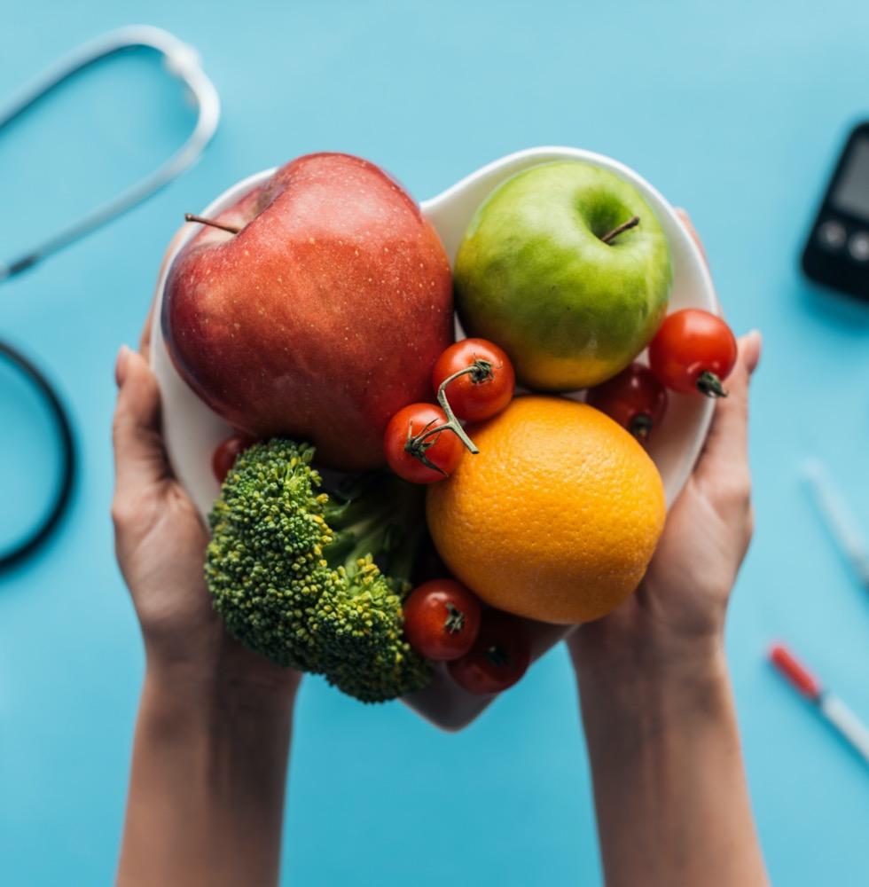 A GP carrying a bowl of fruits and vegetables for a heart healthy diet, Epping Doctors